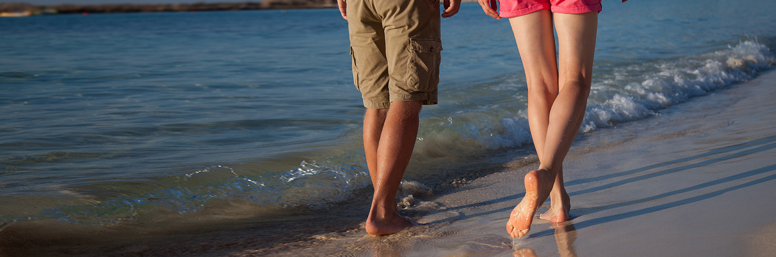 Couple walking on the beach, living a healthier life after varicose vein treatment