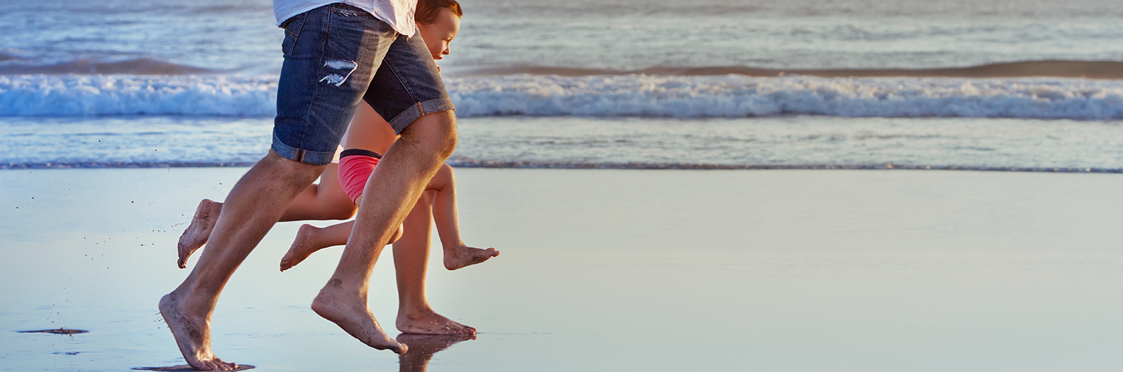 Family running on beach with healthy legs after varicose and spider vein treatment