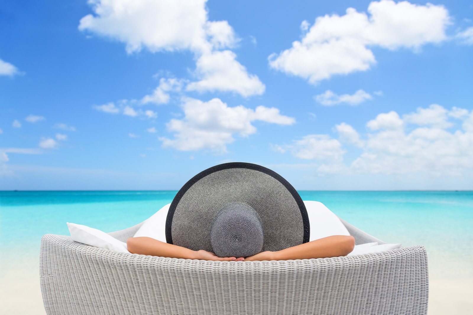 Woman relaxes in chair overlooking the ocean